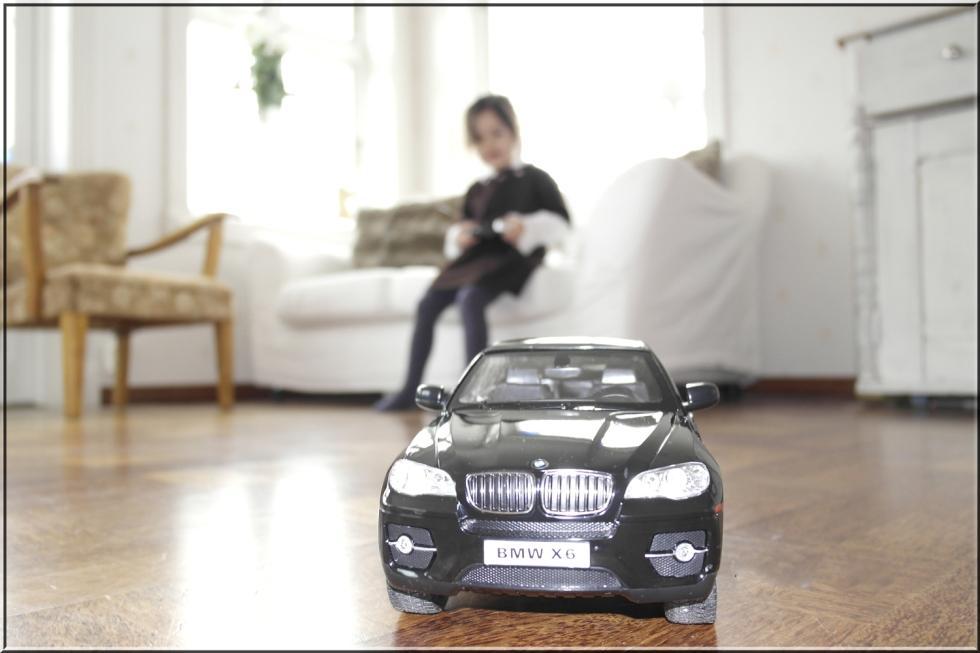 Lykke-Merlot kjører radiostyrt bil i storstuen. Dette er tipp topp en en fireåring.